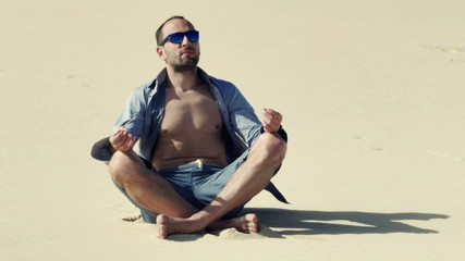 Young man meditating while sitting on desert