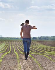 Farmer with hoe in corn field