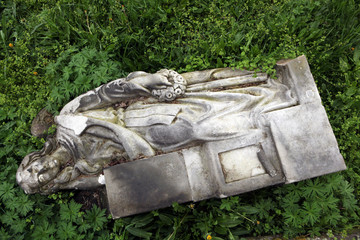 Fallen angel. Destroyed tombstone at the abandoned cemetery.
