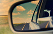Rear view mirror and long road through arid landscape