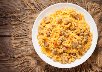 A delicious pilaf in a dish on the old board