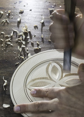 Hands of woodcarver make wooden bowl