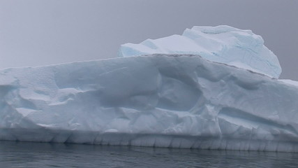 Sailing pass near by big iceberg, Paradise Harbour, Antarctica
