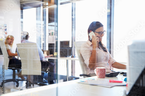Woman talking using phone at her desk in an office