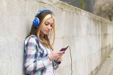 Urban portrait beautiful girl with headphones listening music .