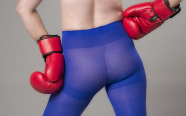 Female boxer wearing red boxing gloves and blue tights