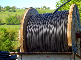 Reel of heavy duty electric cable being unrolled