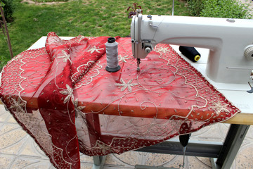 red material with sewing machine in garden