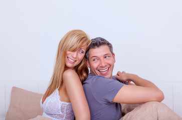 couple sitting bed smiling
