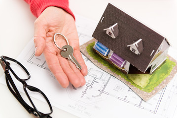 Closeup of woman hand giving residential house key to client