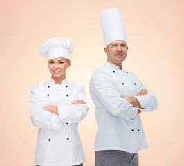 happy chefs or cooks couple over beige background