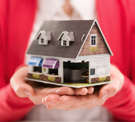 Closeup of woman hands holding house model. Concept of home sale