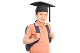 Schoolboy with graduation hat carrying a backpack