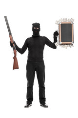 Thief holding bag with money and a shotgun