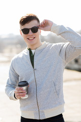 smiling young man or boy drinking coffee