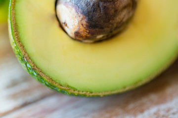 close up of ripe avocado with bone on table