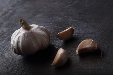 Garlic cloves on the black wooden table