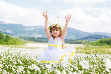 Little girl at field of camomiles