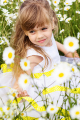 Portrait of child girl at camomile field