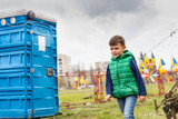 Boy passing near a blue portable toilet in a park