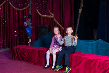 Two young children waiting for a performance