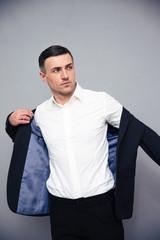 Businessman dressing jacket over gray background