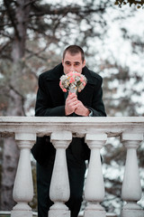 The groom stands near a handrail and holds  a bridal bouquet