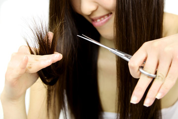 Asian girl chopping split dead ends hair with scissors closeup