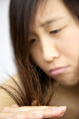 Closeup of ruined damaged hair of asian girl looking