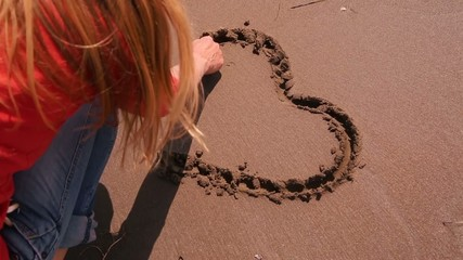 Woman hand drawn lovely heart shape on sandy beach