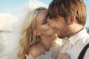 Romantic picture of young bride kissing her husband