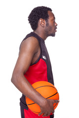Side view of a basketball player holding a basketball, isolated