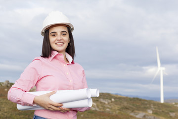 Female engineer holding a plans at wind turbine site