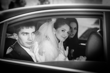 Bride and groom kissing in limousine on wedding-day.