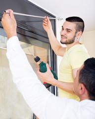 Men hang blinds