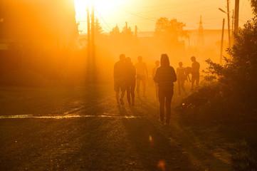 Силуэты людей, идущих по дороге