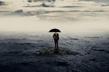 Man Holding Umbrella Stading On The Rock On The Sea