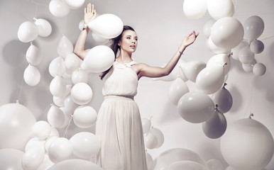 Adorable young woman holding many balloons