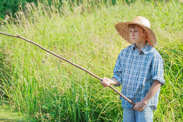 Сoncentrated boy watching after handmade fishing rod