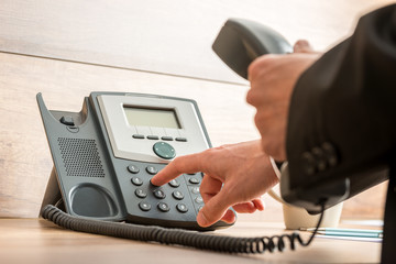 Businessman hand holding a landline telephone receiver dialing a