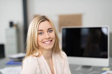 lächelnde auszubildende arbeitet in einem büro