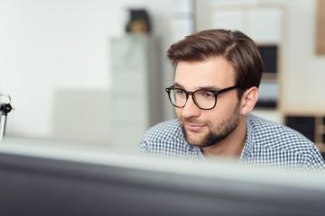 mitarbeiter im büro schaut auf pc-bildschirm