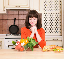 Unhealthy vs healthy food concept - woman choosing vegetables