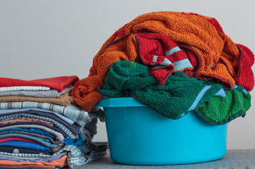 Stack of clothes and a basket with wet towels