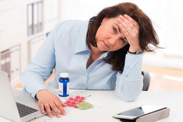gestresste geschäftsfrau mit medikamenten