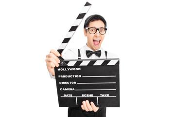 Retro guy posing behind a movie clapperboard