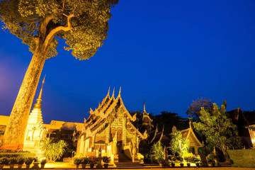 Thai art pavilion with large teak in Wat Jedi Luang under twilig