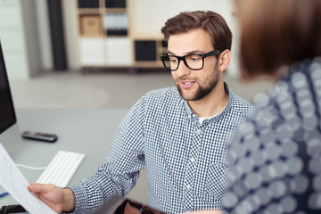 zwei mitarbeiter unterhalten sich am schreibtisch