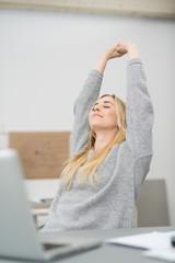 zufriedene frau im büro streckt die arme nach oben