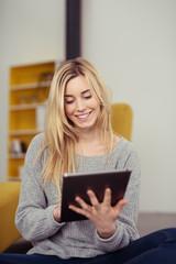lächelnde junge frau tippt auf tablet-pc in ihrer wohnung